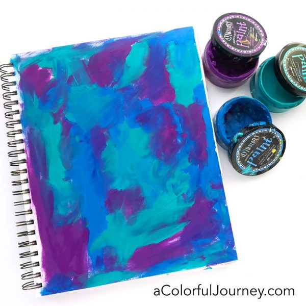 Video finger painting a peacock colored background in an art journal with Carolyn Dube