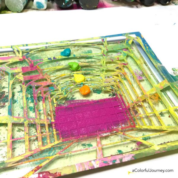 Gel printing with a stencil into an art journal to create a rainbow room tutorial by Carolyn Dube